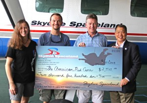 Skydive Spaceland marketing director Christy West, general manager Jason Hyder, and owner Steve Boyd present Dave Dunn of the Red Cross with a check for $2,510 to aid tornado victims in Oklahoma.
