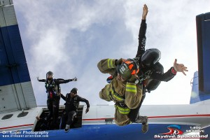 Houston Fire Department firefighter Chris Lee exits the plane for the memorial jump with Jason Hyder.