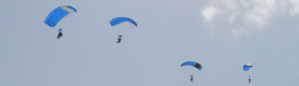 Tandem skydivers under parachutes